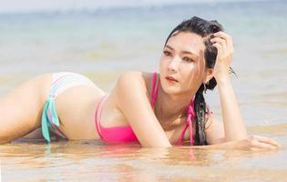 Hermosa mujer asiática descansando en la playa felizmente