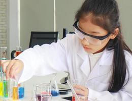 Joven estudiante haciendo experimentos científicos con un tubo químico en un laboratorio foto