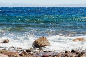 olas chapoteando en una roca foto