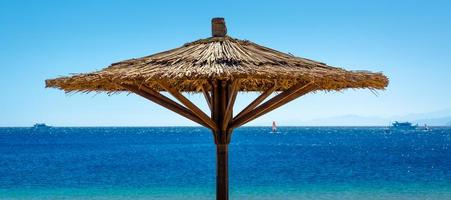 Sombrilla de playa de caña contra el mar azul en Egipto