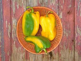 Green and yellow bell peppers on a wicker plate on a wooden table background