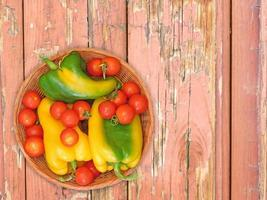 Pimientos y tomates verdes y amarillos en un plato de mimbre sobre un fondo de mesa de madera foto