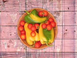 Green and yellow bell peppers and tomatoes on a wicker plate on a wooden table background