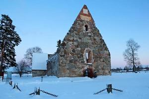 Antiguas ruinas de la capilla medieval europea en la nieve. foto