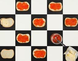 Salmon caviar canapes, butter, red caviar in a jar forming a pattern on chess board, top view photo