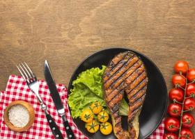 Grilled fish with lettuce, top view photo