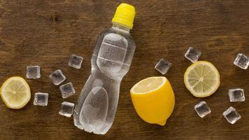agua embotellada de plástico con limón foto