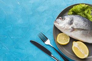 Flat lay fish on blue background photo