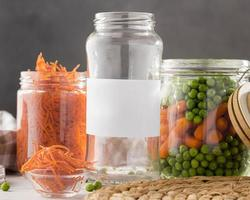 Front view of pickled peas and baby carrots in clear glass jars photo