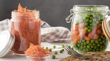 Vista frontal de guisantes en escabeche y zanahorias pequeñas en frascos de vidrio transparente foto