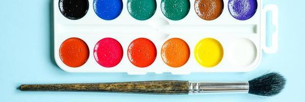 Caja de pinturas de acuarela y pinceles para dibujar sobre fondo azul. foto