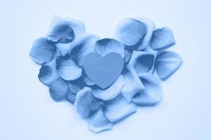 S t. día de San Valentín. el corazón está cortado de papel sobre el fondo de pétalos de rosa. tendencia de color azul clásico teñido año 2020 foto