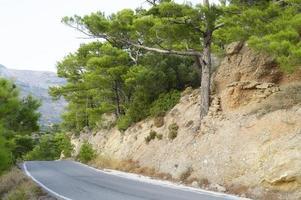 Carretera asfaltada en las montañas mediterráneas cubiertas de pinos foto