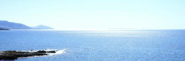 paisaje marino con montañas y rocas al amanecer, hermosa agua azul y cielo foto