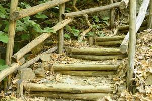 Old homemade wooden staircase that runs over rocks in a mountain gorge