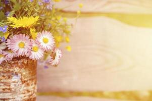 A bouquet of wildflowers of forget-me-nots, daisies and yellow dandelions in full bloom in a rustic jar photo