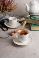 Still life with tea splashing out of tea cup, books, and flowers photo