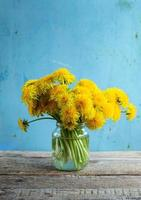 Bouquet of dandelions in glass jar on wooden table with light blue backdrop