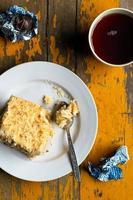 Milhojas caseras, tarta de crema pastelera de hojaldre sobre placa blanca, chocolates, taza de té sobre fondo de madera pintada de amarillo antiguo foto