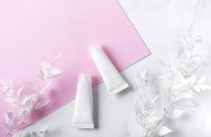 Tubos blancos de crema sobre un fondo de mármol y rosa foto