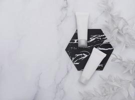 Tubos de crema blanca sobre un fondo de mármol foto