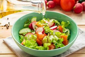 Fresh vegetable salad with cucumbers, radishes, and olive oil photo