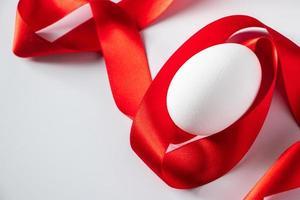 huevo blanco con cinta de seda roja foto