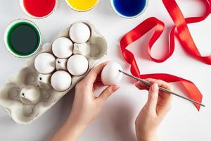 Young woman paints white eggs for easter photo