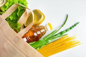 Groceries in a reusable grocery bag on white background