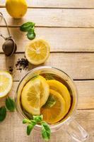 Té de hierbas con limón y menta sobre fondo de madera foto