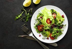 Fresh green mixed salad bowl with tomatoes and microgreens on black concrete background photo