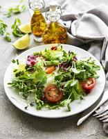Fresh green mixed salad bowl with tomatoes and microgreens on concrete background photo