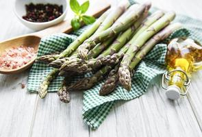Bunch of raw asparagus stems with different spices photo