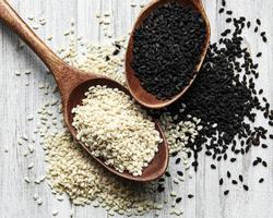 Black and white sesame seeds in spoons