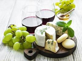 Various types of cheese, grapes and wine photo