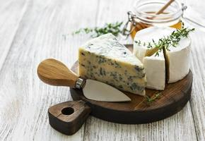 Various types of cheese, blue cheese, brie, camembert, and honey on a wooden table photo