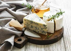Various types of cheese, blue cheese, brie, camembert, and honey on a wooden table