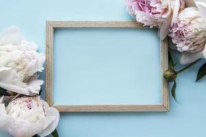 Marco de madera rodeado de hermosas peonías rosas sobre un fondo azul. foto