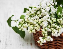 Cesta con flores lilas blancas sobre un fondo de madera foto