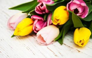 Ramo de tulipanes rosados y amarillos sobre un fondo de madera foto