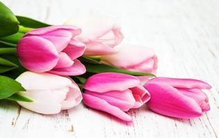Ramo de tulipanes rosas sobre un fondo de madera vieja foto