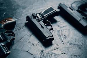 tres pistolas en la mesa negra foto
