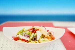 Ensalada vegetariana en plato de cerámica sobre mesa de rafia blanca foto