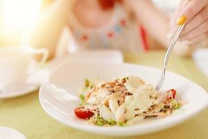 Woman's hand holds fork in a plate of salad