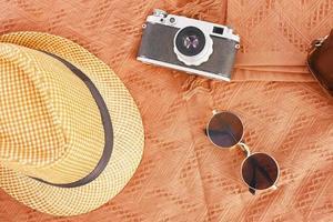 Hat, camera, glasses on the carpet photo