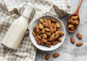 Glass bottle with almond milk and almonds on the table photo