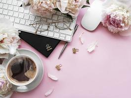 Flat lay top view women's office desk with flowers and accessories on a pink background photo