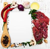 Meat steaks, a recipe book, and ingredients on an old wooden background photo