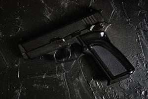 Gun on black texture table photo