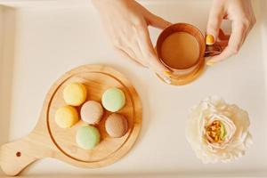 Mug of coffee in woman's hands and wooden tray with macaroons photo